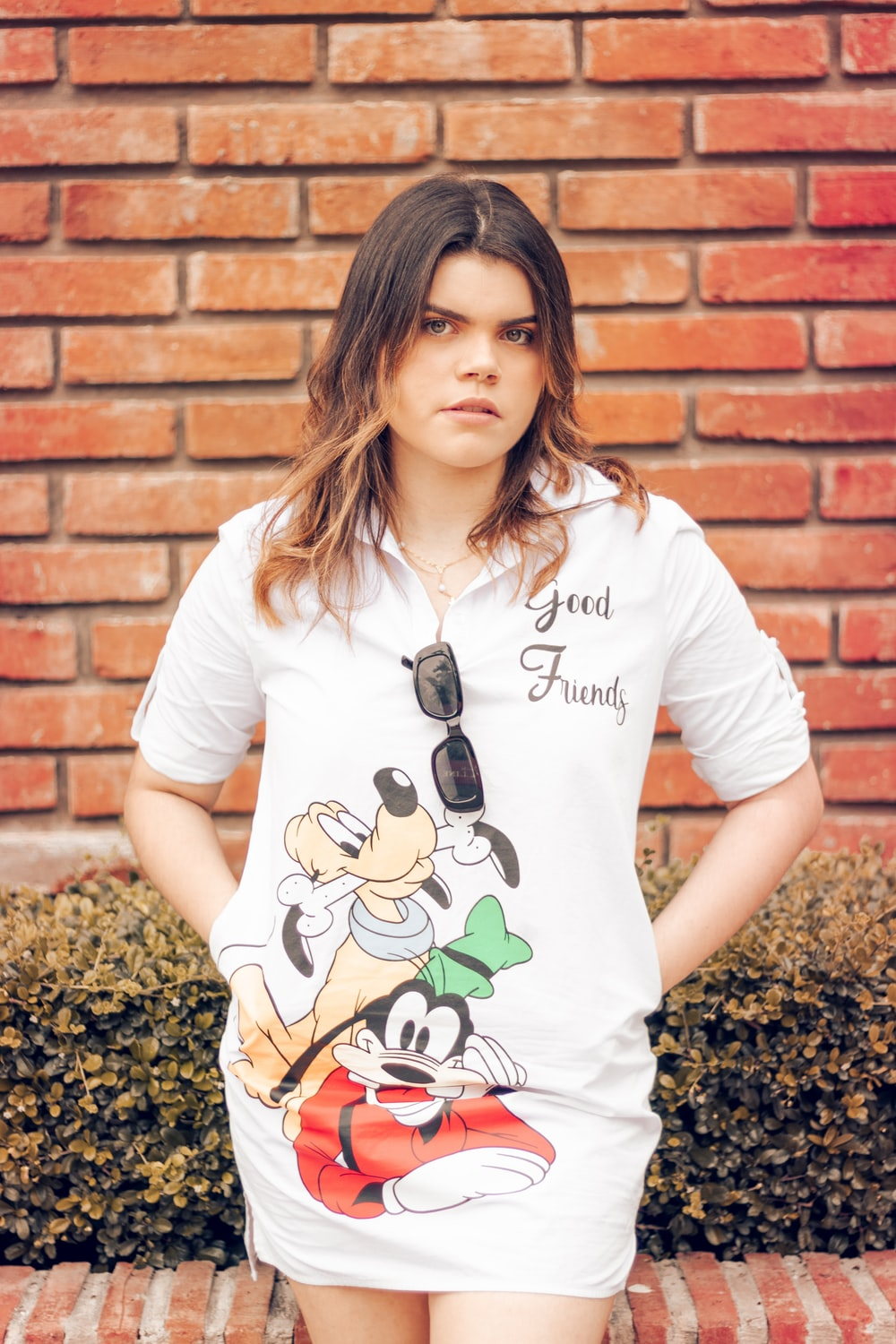 woman in white crew neck t-shirt standing beside brown brick wall