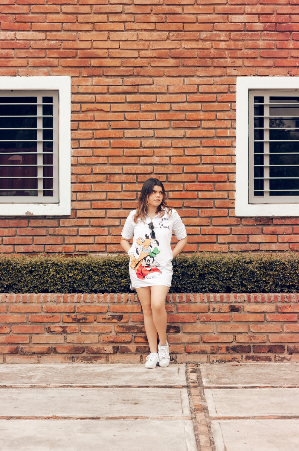 woman in white t-shirt and white shorts standing beside brown brick wall