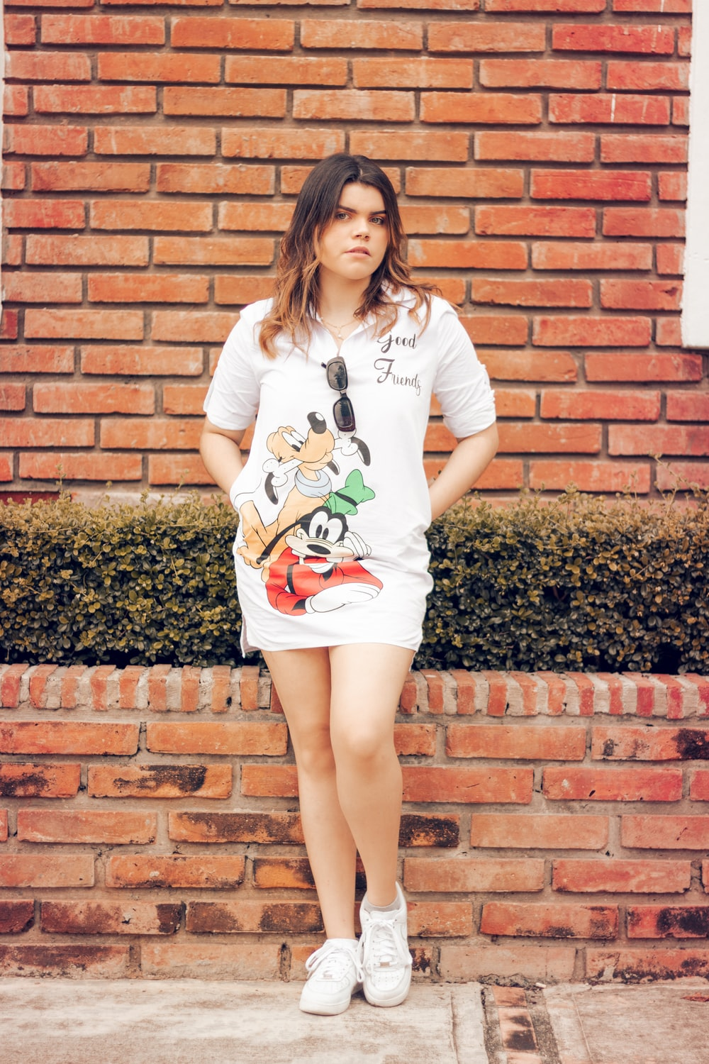 woman in white crew neck t-shirt and white skirt standing beside brown brick wall