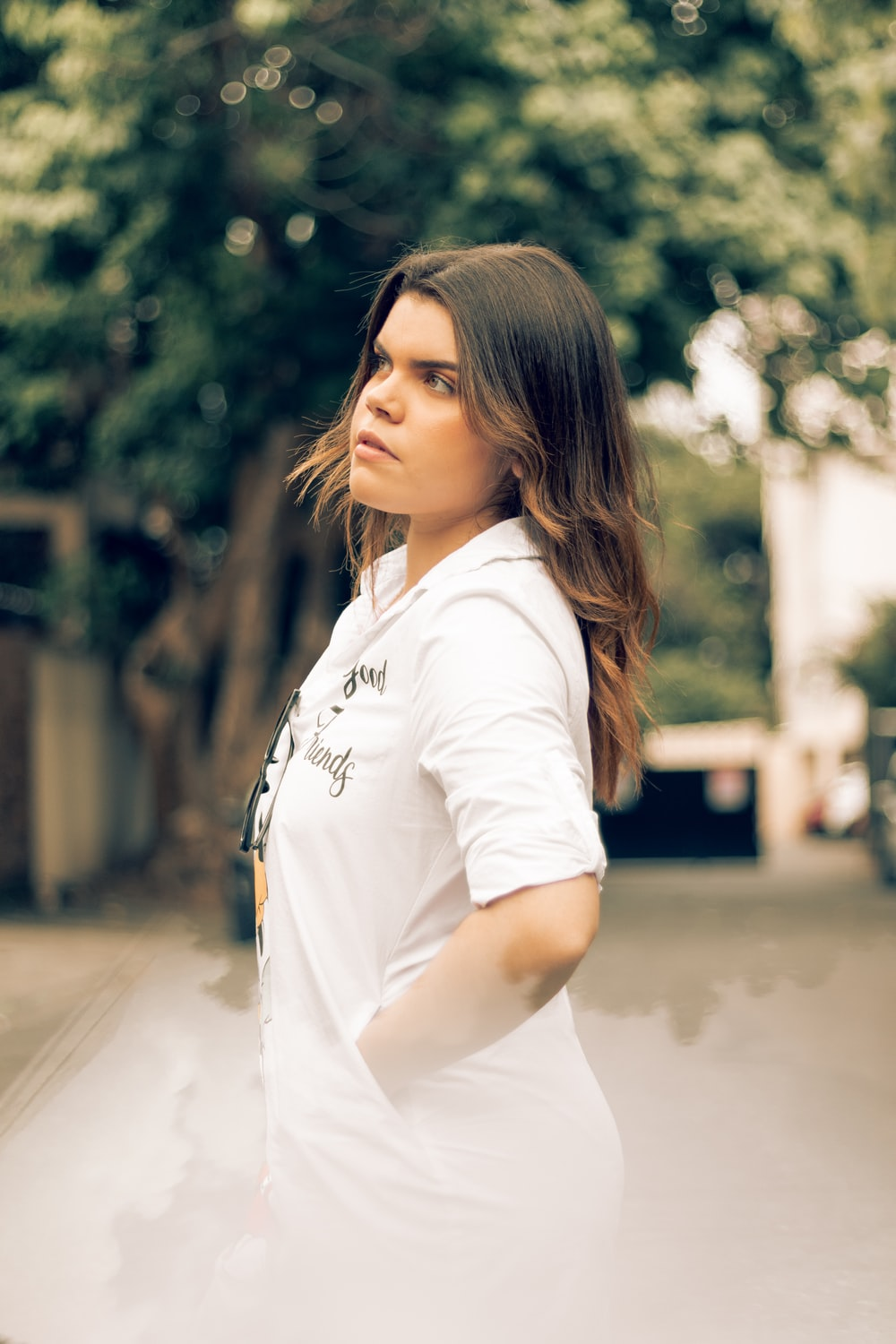 woman in white polo shirt standing on road during daytime