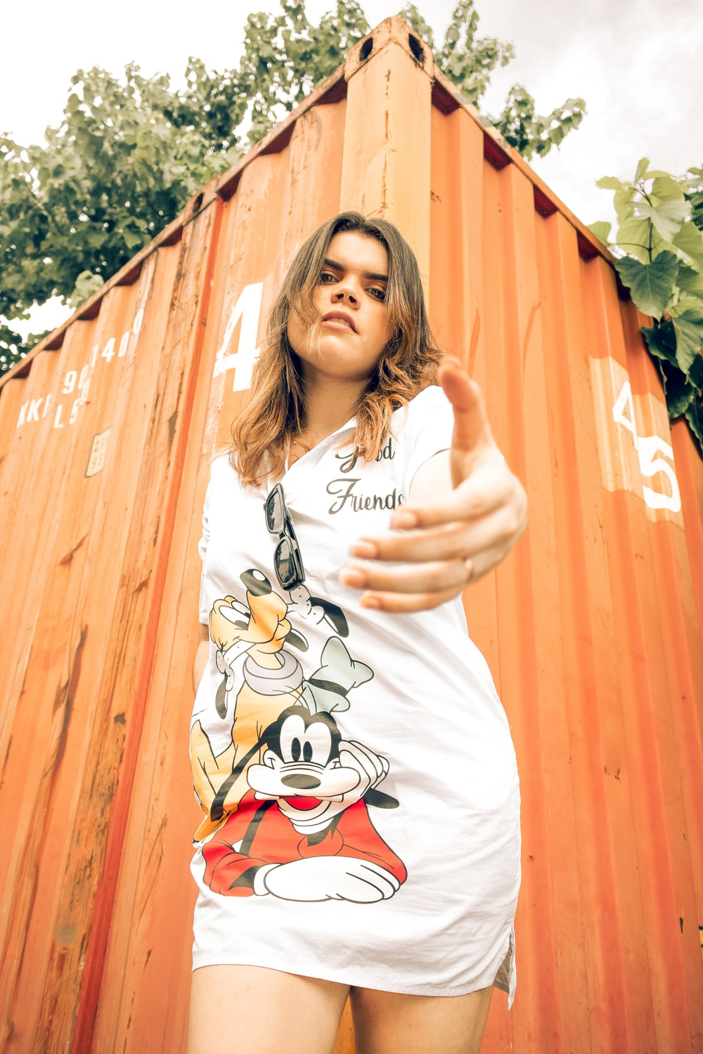 woman in white mickey mouse shirt standing beside brown wooden wall during daytime