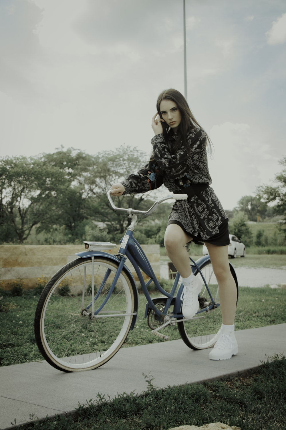 woman in black dress riding blue bicycle during daytime
