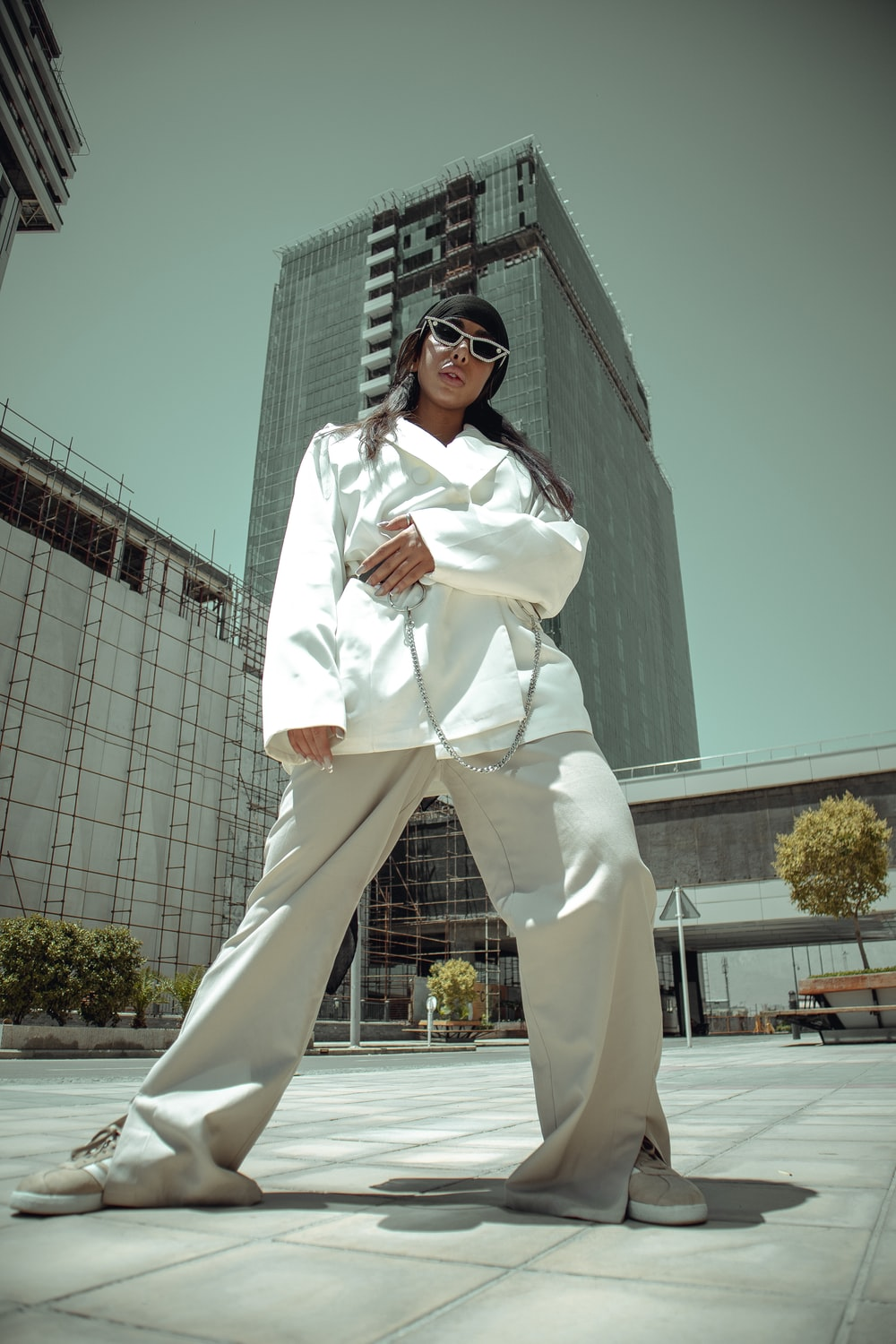 woman in white long sleeve shirt and white pants standing near white building during daytime