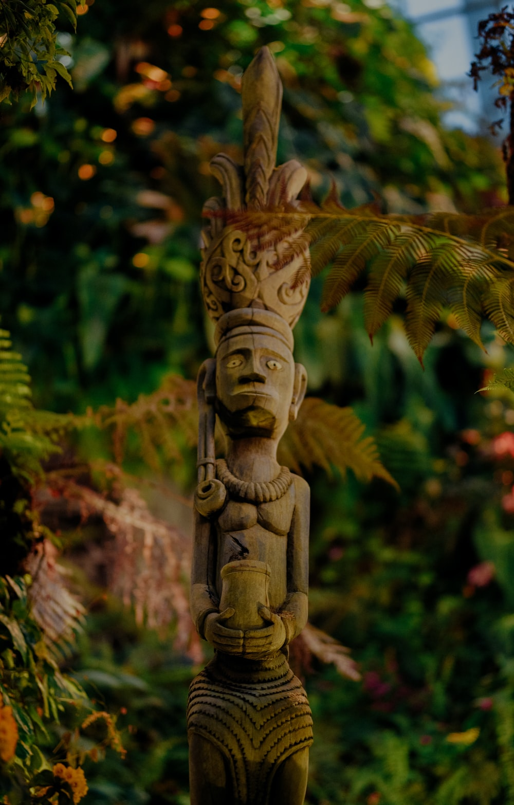 brown wooden statue near green plants during daytime