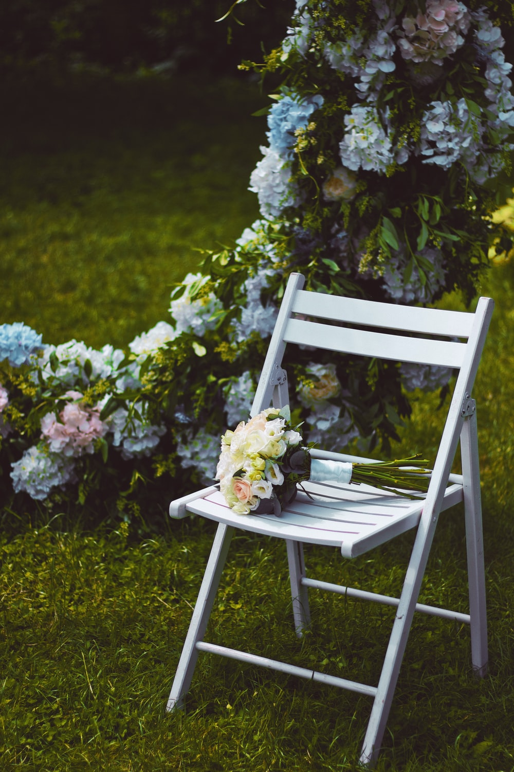 white and yellow flowers on white wooden chair