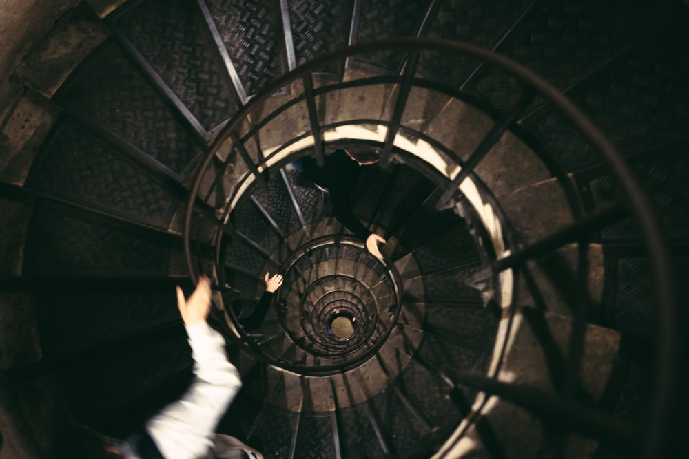 person in white long sleeve shirt and white pants walking on spiral staircase
