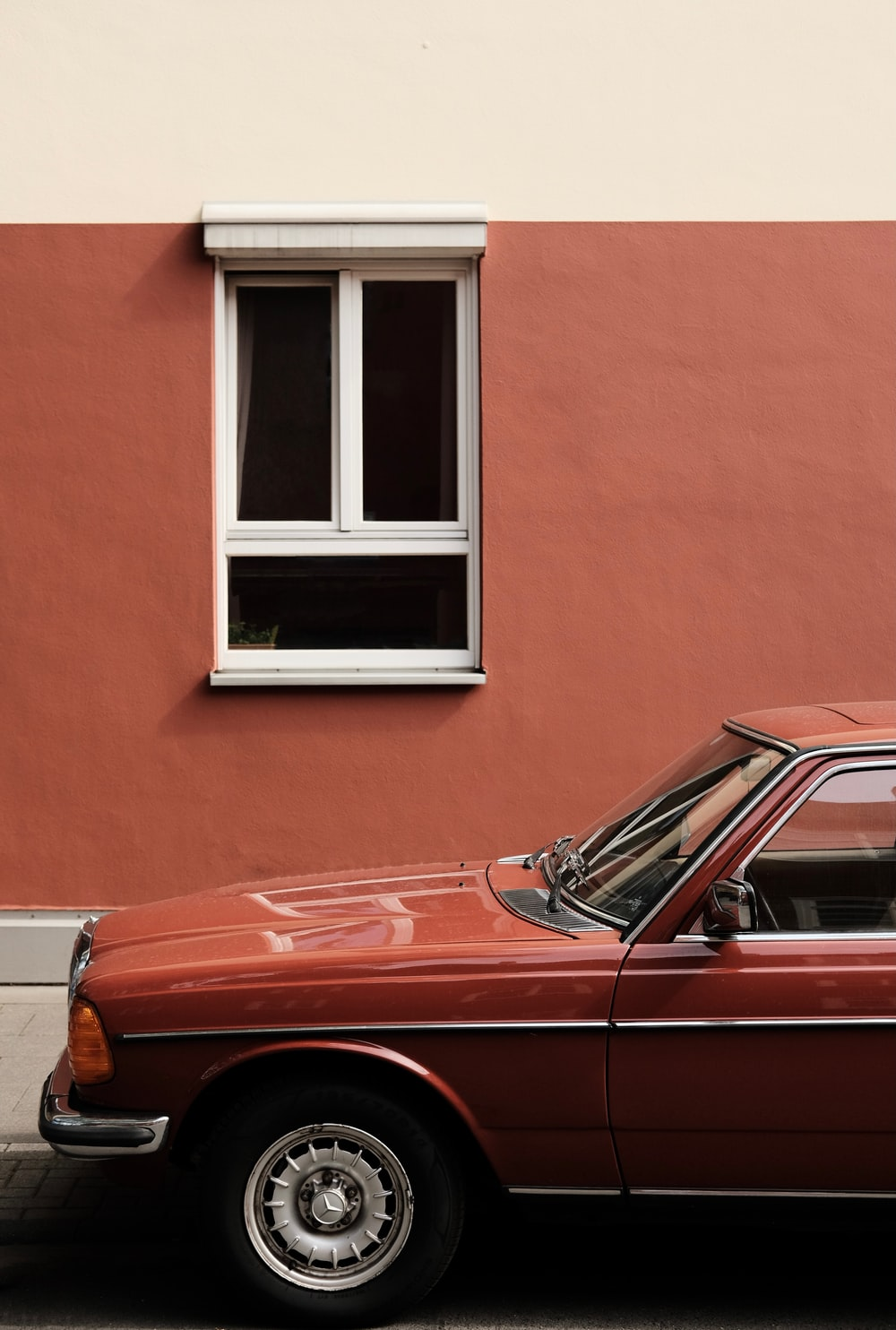 red car parked beside brown concrete building