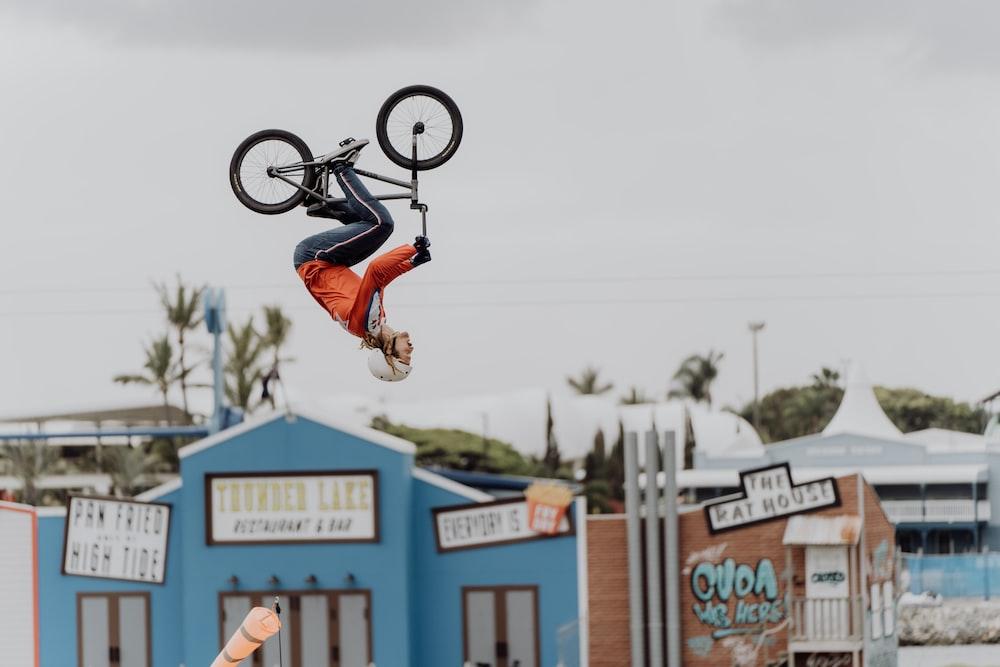 man in black and orange jacket riding black bmx bike doing stunts during daytime