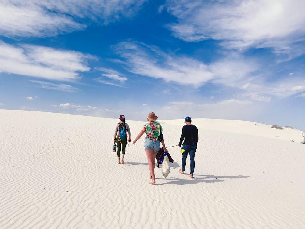 3 women walking on sand during daytime