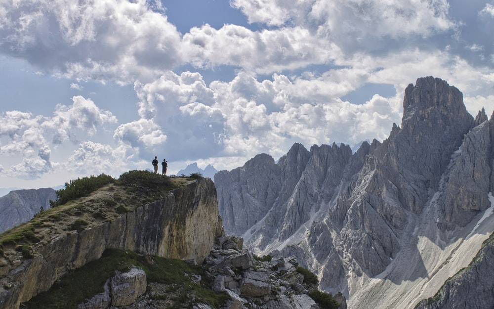 person standing on rocky mountain under white clouds during daytime