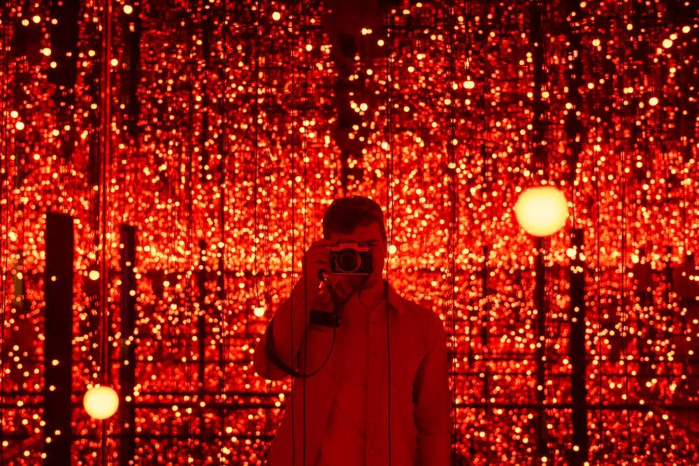 man in red hoodie wearing black sunglasses