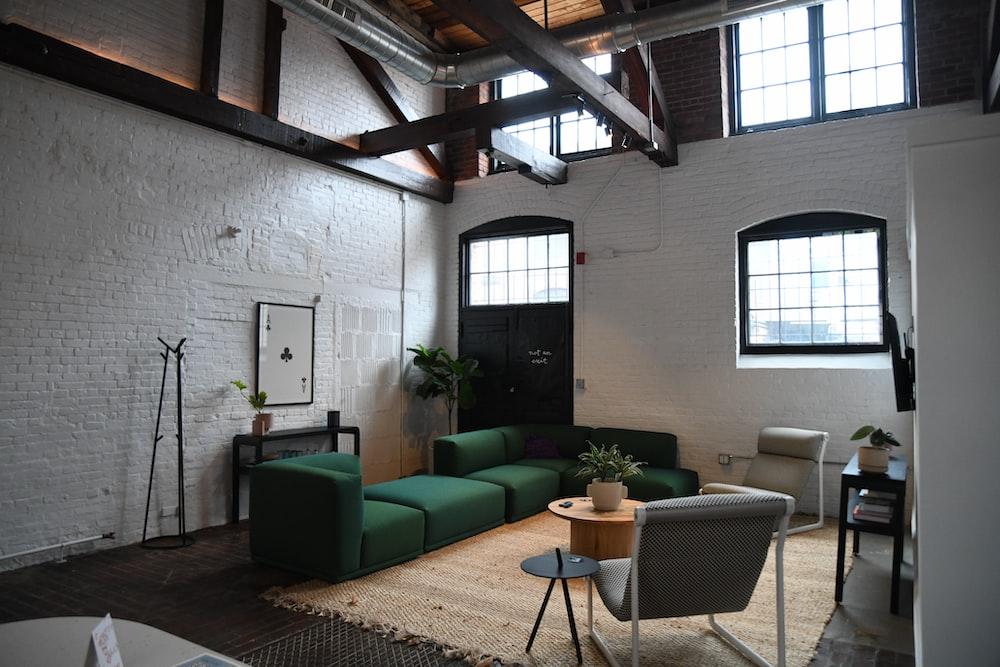 green sofa set near window