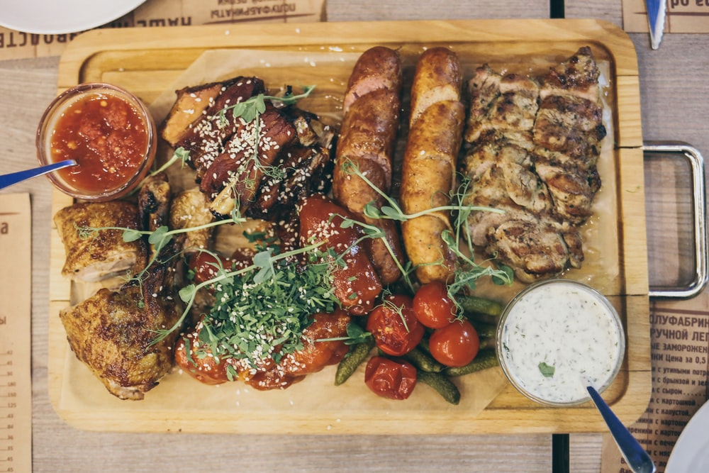 grilled meat with green vegetable and tomato on brown wooden tray