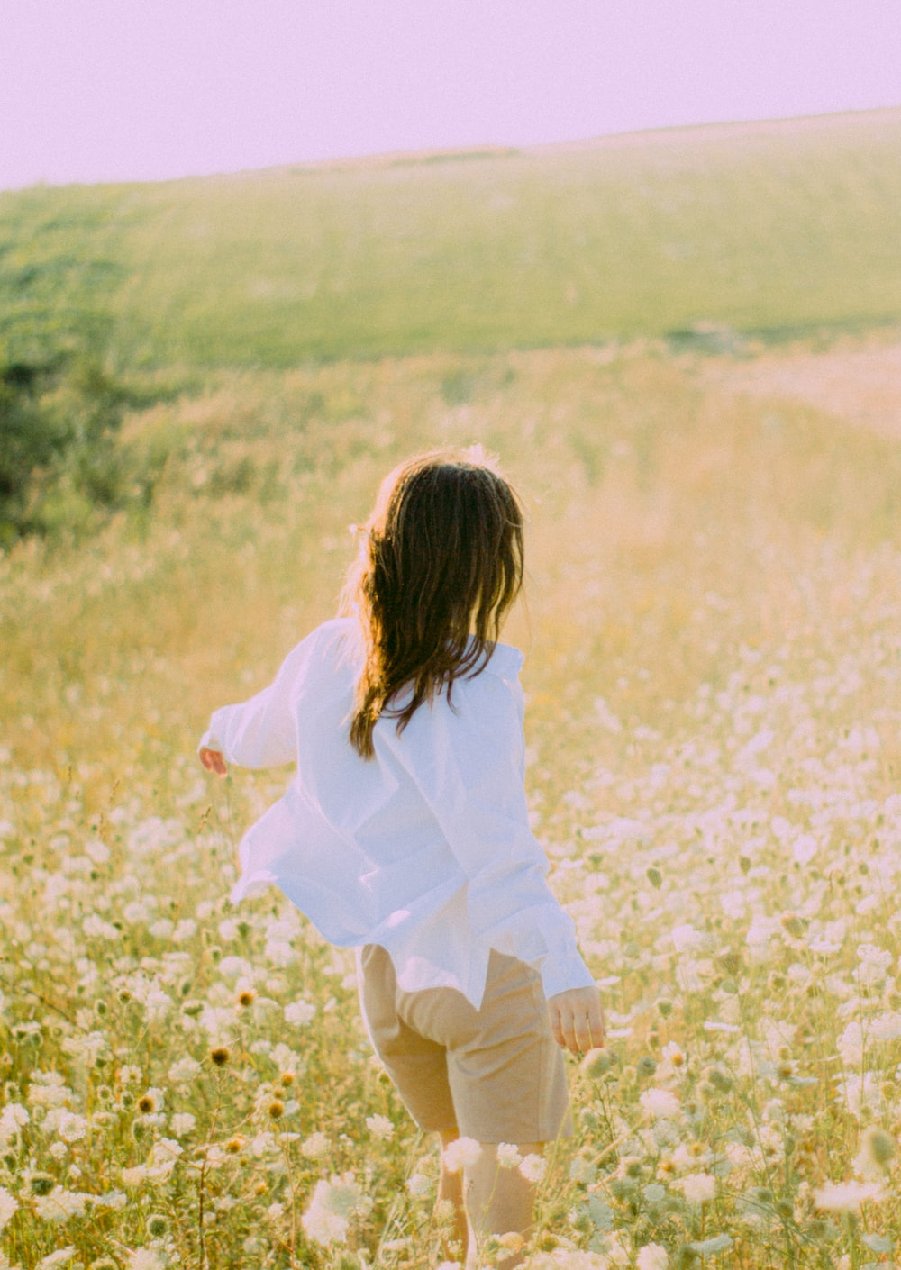 woman in white dress shirt and brown pants walking on yellow flower field during daytime