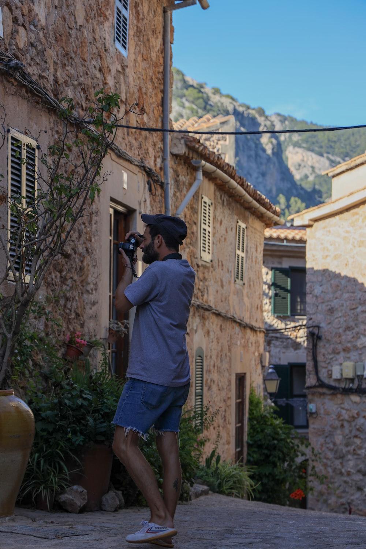 man in gray t-shirt and blue shorts holding black dslr camera