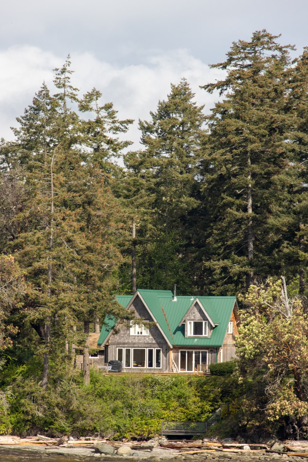 green and white wooden house surrounded by green trees under white clouds and blue sky during
