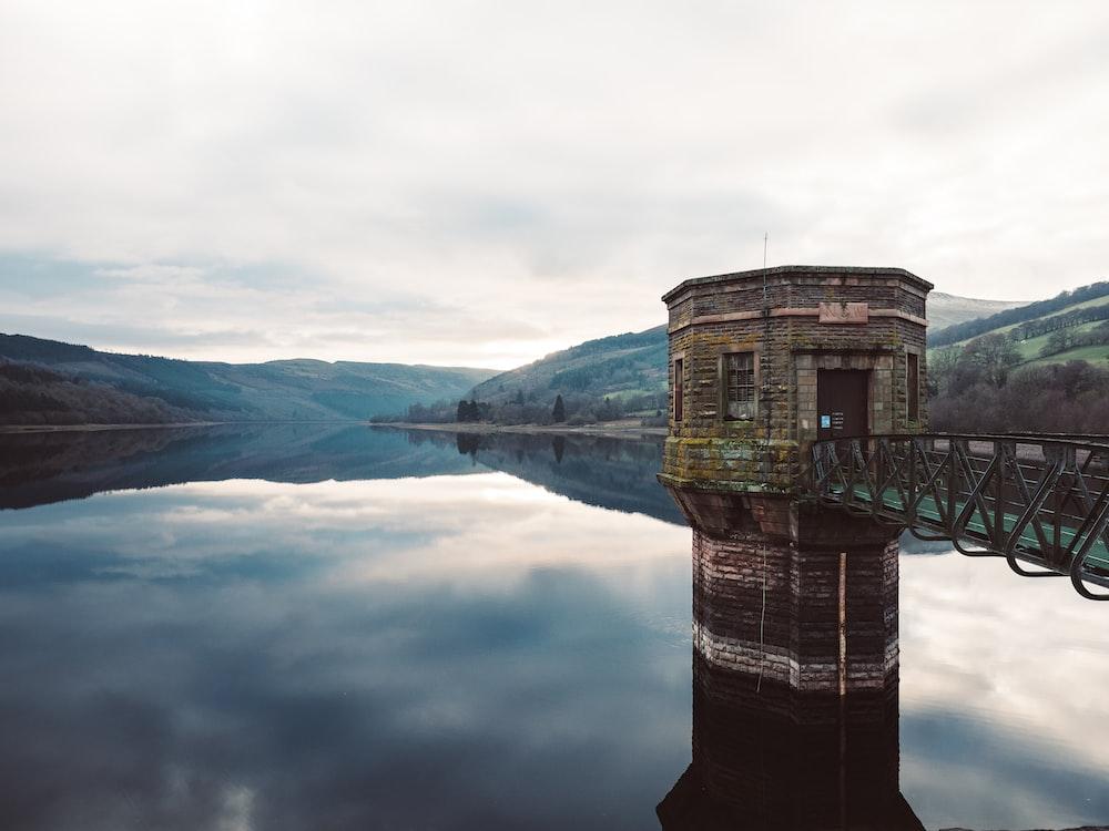 brown concrete building on lake during daytime