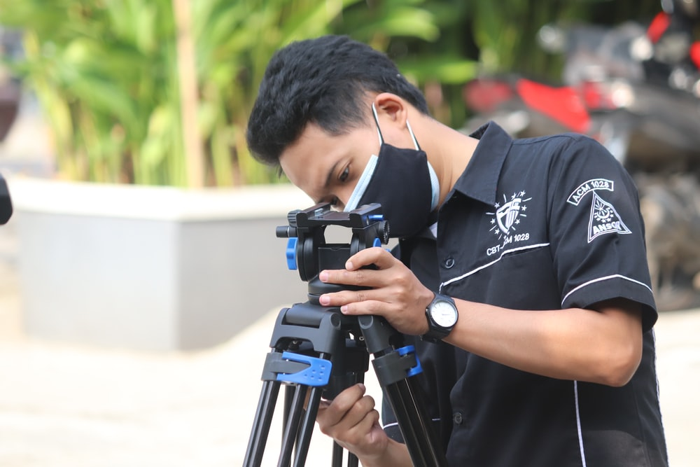 man in black and white crew neck t-shirt using black dslr camera during daytime