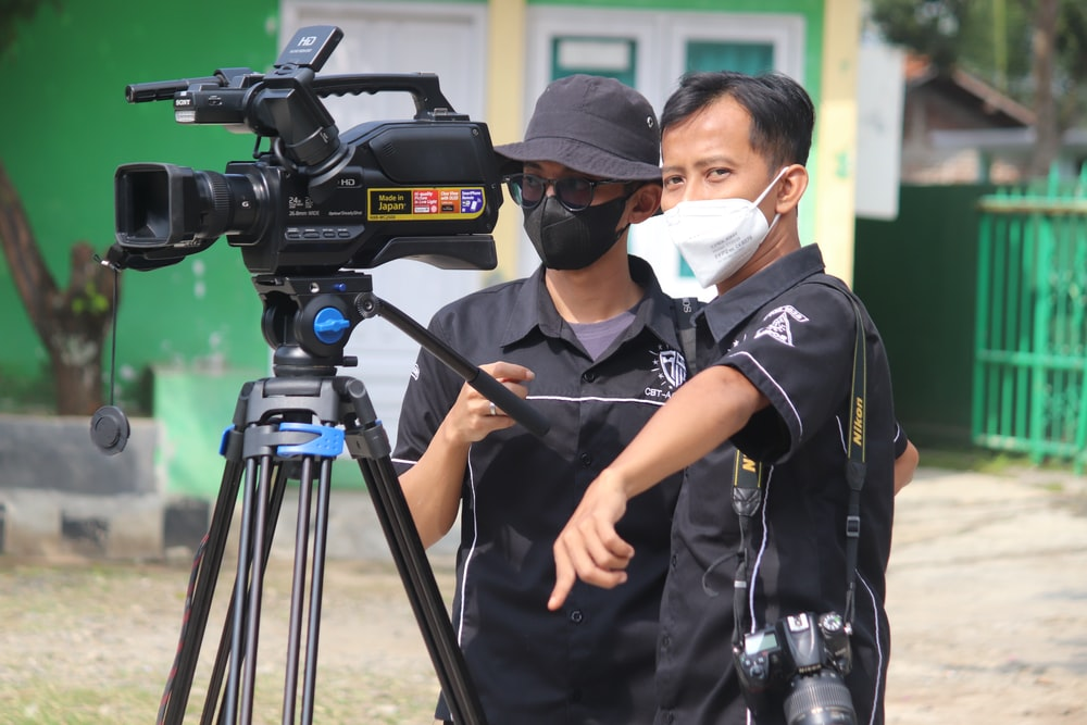 man in black polo shirt wearing white mask holding black camera