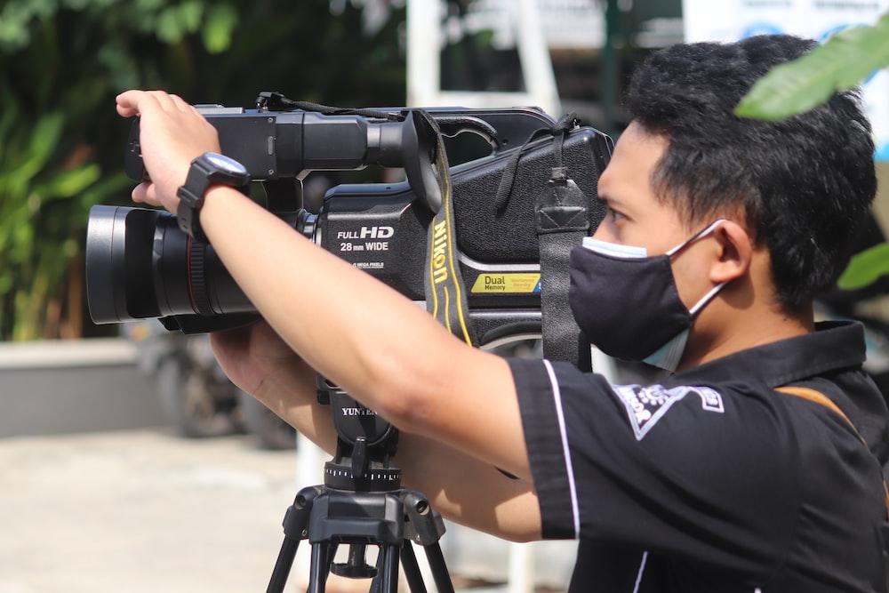 man in black and white t-shirt holding black dslr camera