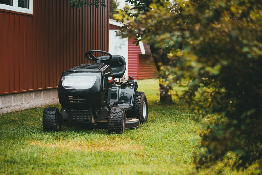 black ride on lawn mower on green grass field during daytime