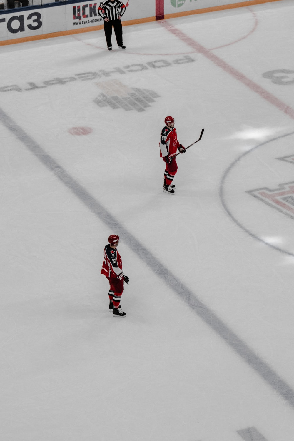 man in red and white jersey shirt and pants playing ice hockey