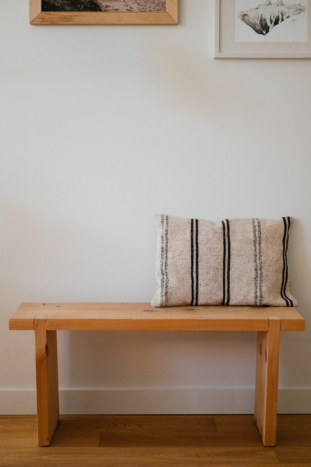 white and blue throw pillow on brown wooden chair