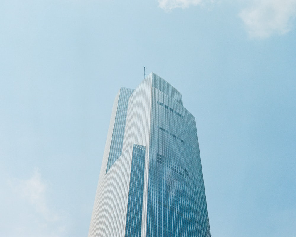 white high rise building under white clouds during daytime