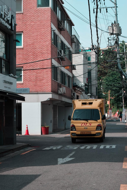 yellow van parked in front of brown building