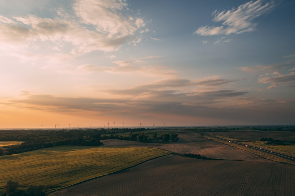 brown field under white clouds during daytime