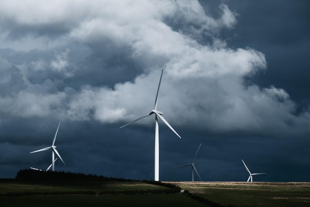 white wind turbines on green grass field under gray clouds