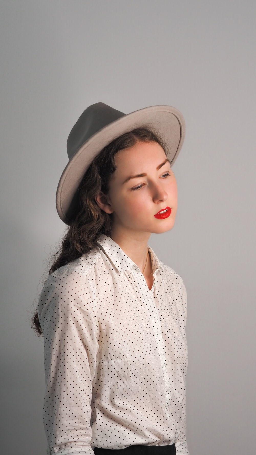 woman in white and black button up shirt wearing brown hat