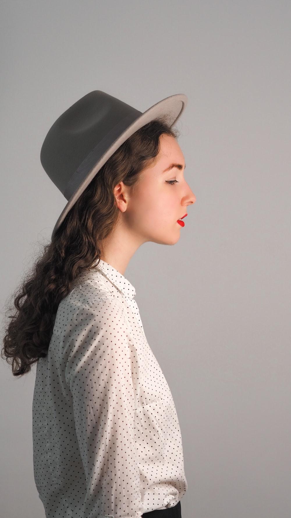 woman in white and black polka dot shirt wearing black hat