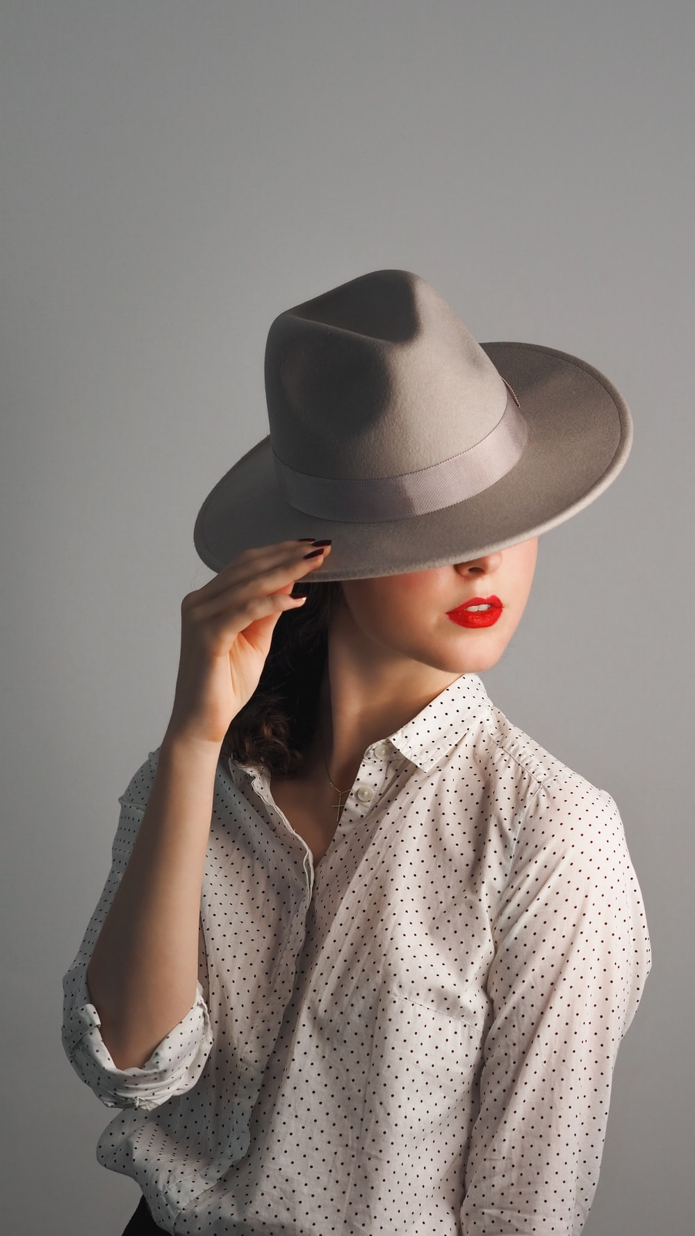 woman in grey hat and grey button up shirt