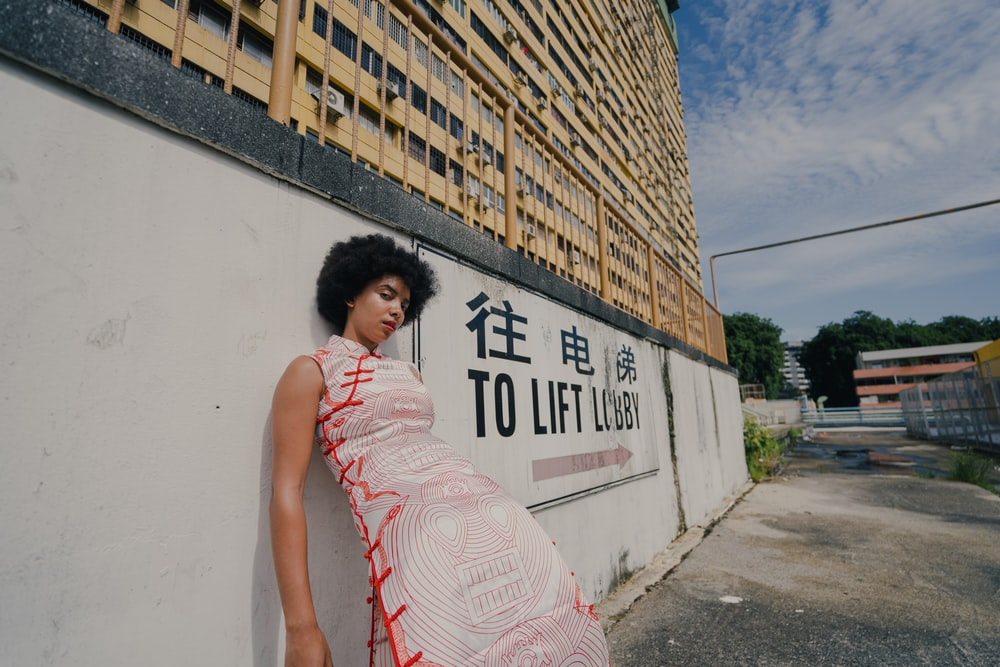 woman in pink and white sleeveless dress standing beside wall with graffiti during daytime
