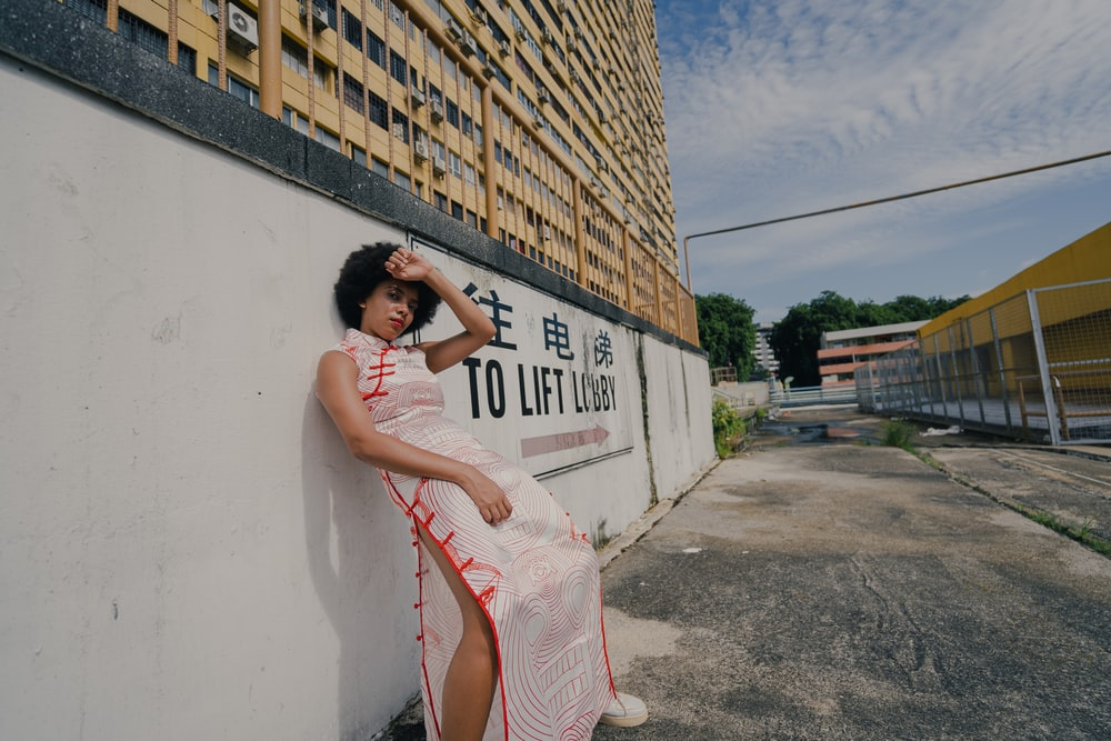 woman in white and pink dress leaning on white wall