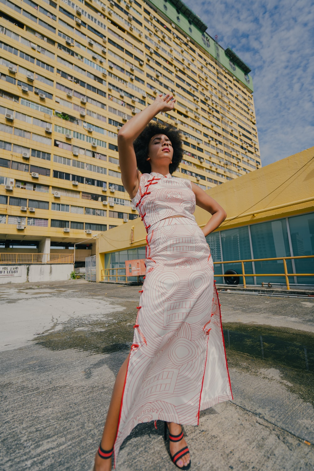 woman in white and red floral dress standing on gray concrete floor during daytime