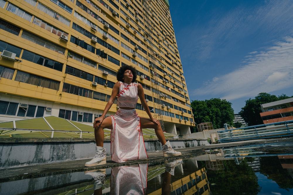 woman in white dress sitting on concrete bridge during daytime