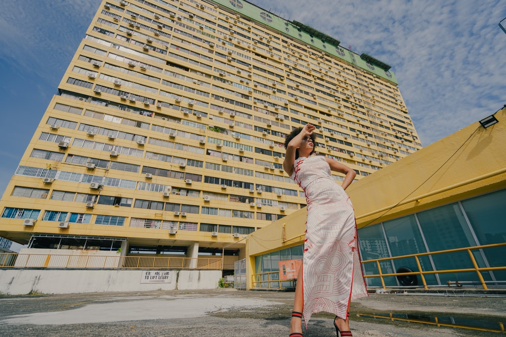 woman in white dress standing near beige concrete building during daytime