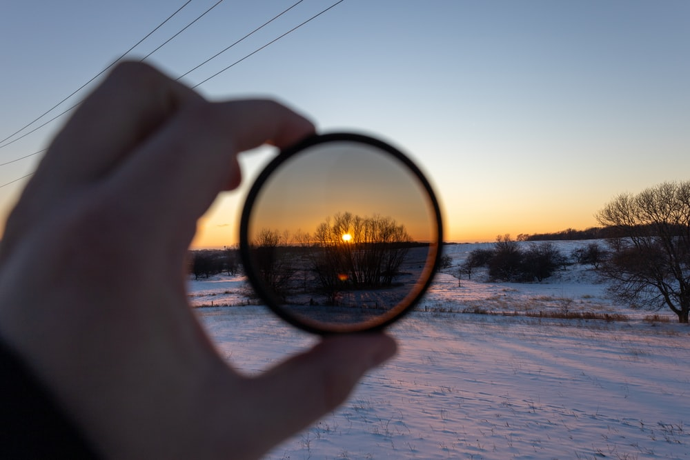 person holding magnifying glass during sunset