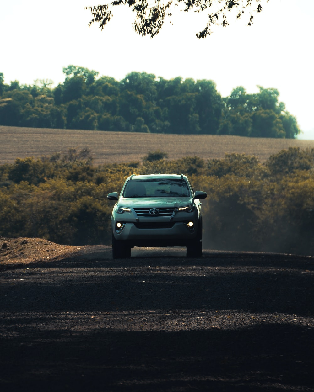 gray car on dirt road during daytime