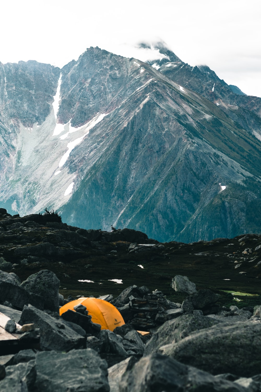 yellow dome tent on rocky ground near mountain