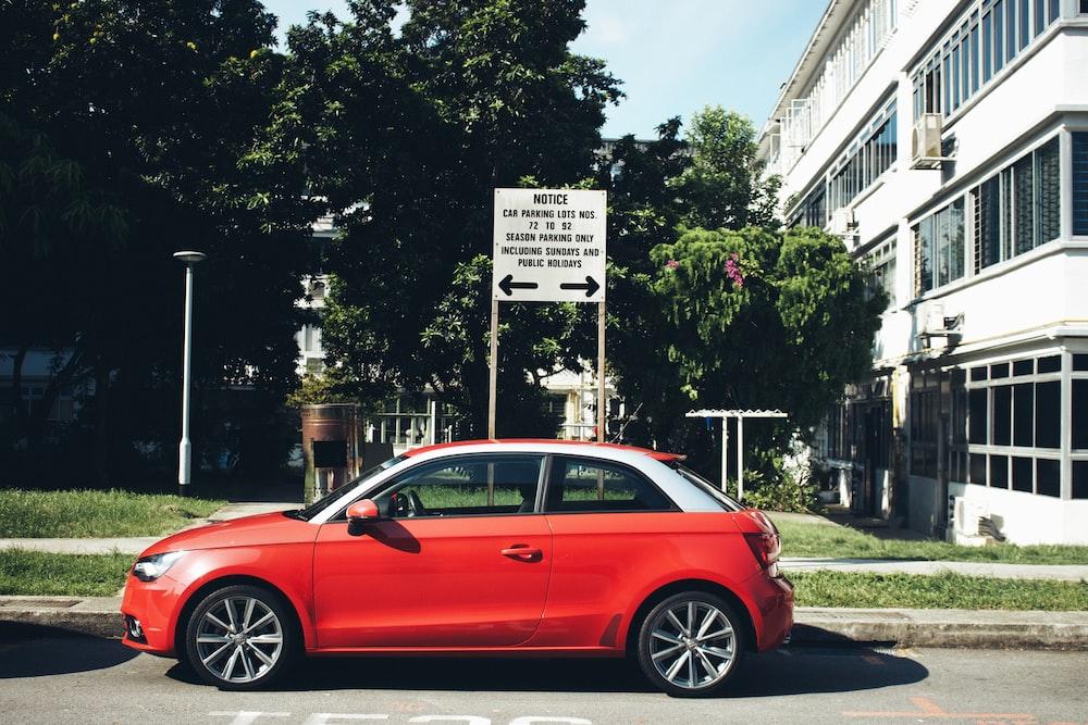 red sedan parked near white building during daytime