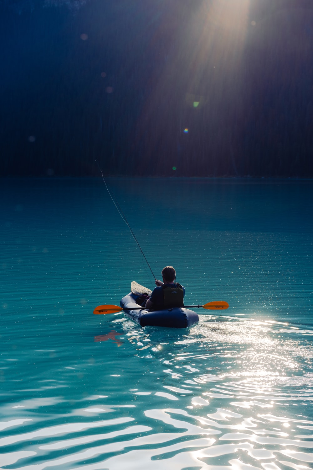 person riding on kayak on body of water during daytime