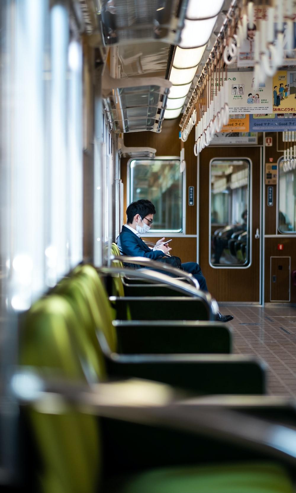 man in blue dress shirt sitting on train seat