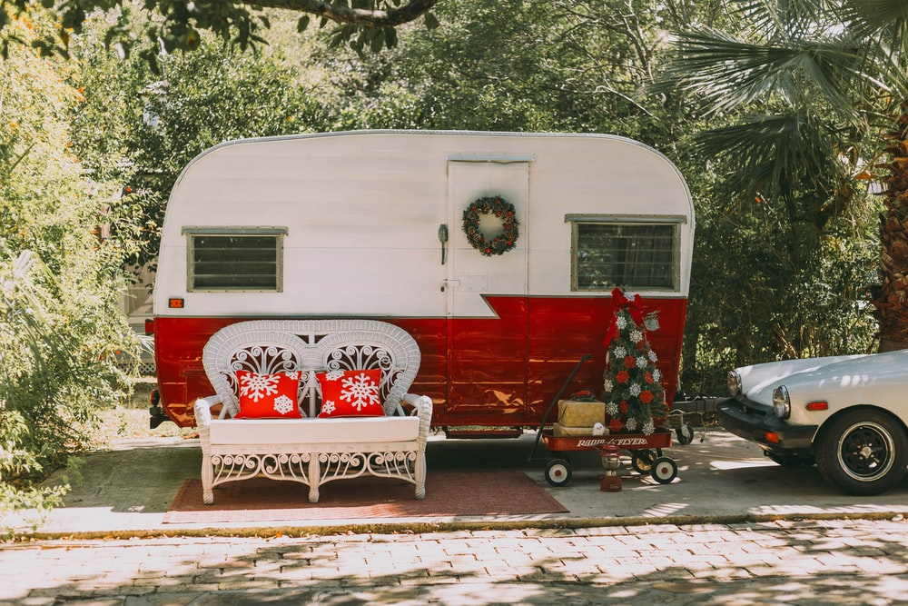 red and white bicycle parked beside white and red rv trailer