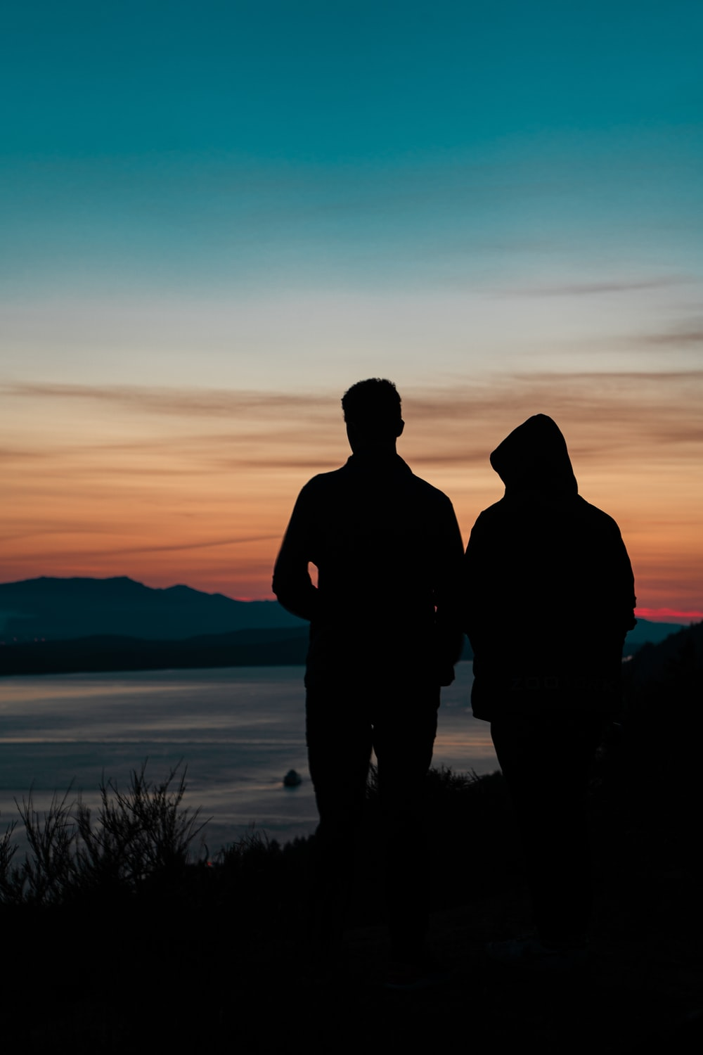 silhouette of man and woman standing near body of water during sunset
