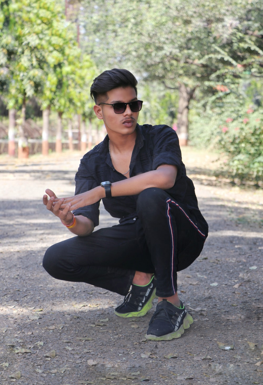 man in black t-shirt and black pants sitting on road during daytime