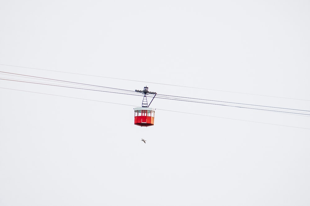 red cable car under white sky