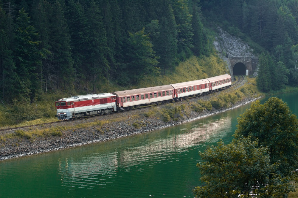 red and white train on rail near river during daytime